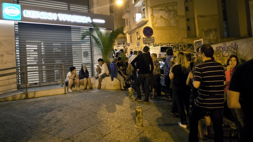 People queue in front of an ATM mache to withdraw cash from a National Bank of Greece in central Athens