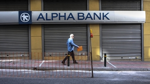 A man walks past a closed bank in Athens today