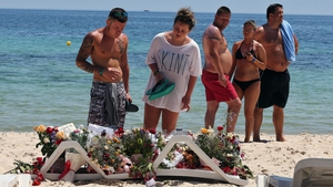 People gather to lay flowers on the beach where 39 people were killed in the terrorist attack
