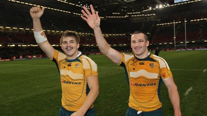 Drew Mitchell (L) and Matt Giteau (R) wave to Australian fans following a game in 2009
