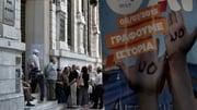 A referendum banner reads 'NO, we are writing history' as pensioners queue outside a bank to withdraw a limited amount of €120 per person in Athens