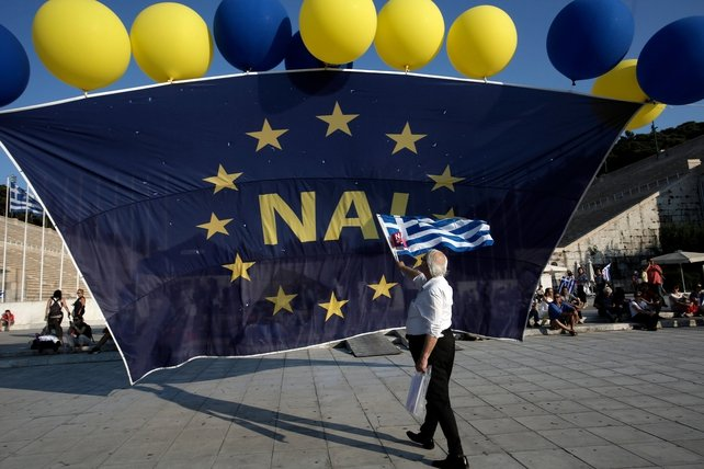 A protester holds a Greek flag in front of a giant European flag with the word 'YES' printed on it during a rally supporting a 'Yes' vote in the referendum and demanding Greece to remain in the Eurozone, at the ancient Panathenaic Stadium, in Athens