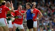 Mark Collins of Cork reacts as referee Padraig Hughes awards a penalty against him in the Munster football final