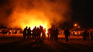 People stand near a small bonfire in the New Mossley area of Belfast