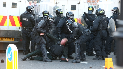 A police officer is dragged away after being struck by an object thrown by loyalist protesters