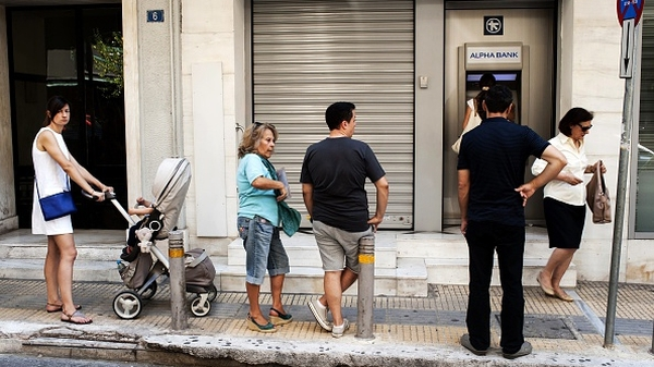 People wait in line to withdraw cash from an ATM machine in Athens