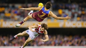 Jed Adcock of the Lions and Nick Smith of the Swans collide during the round 15 AFL match between the Brisbane Lions and the Sydney Swans at The Gabba