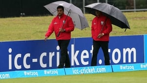 The umpires inspect the rain-soaked outfield at Malahide