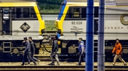 Migrants walk along railway tracks at the Eurotunnel terminal  in Calais