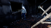 A Palestinian walks through the gutted house in the West Bank village of Douma