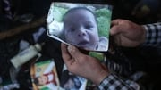A man shows a picture of Ali Saad Dawabsha who died in the fire