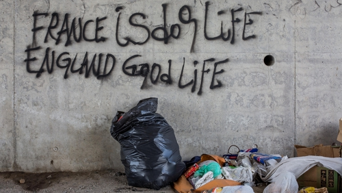 Graffitti reading 'France is dog life, England is good life' is scrawled on a wall