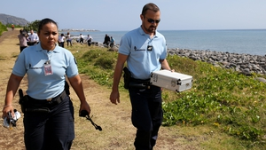 Police officers leave the scene with container holding metallic debris found on a beach on Reunion