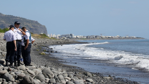 Police search a beach on Reunion where debris has washed up