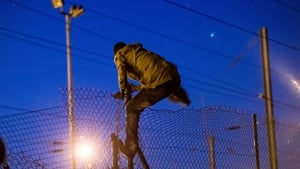 A migrant climbs a fence to enter the Channel Tunnel site
