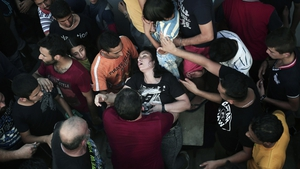A woman faints as hundreds wait for immigration papers in Kos