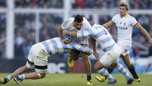 South Africa's Damian de Allende resists a tackle by Benjamin Macome and Santiago Garcia Botta of Argentina