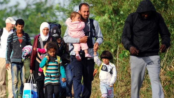 Migrant families walk between rails near the border village Roszke, at the Hungarian-Serbian border