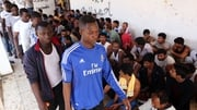 People rescued by Libyan coastguard after their boat sank on August 28, 2015, sit in a security centre