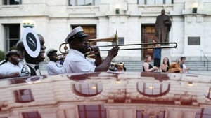 A marching band winds through the streets of the French Quarter during anniversary commemorations