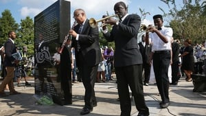 A jazz funeral procession passes the Hurricane Katrina Memorial
