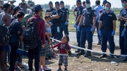 Hungarian police stand guard over Syrian refugees as they wait to be taken to a reception centre having crossed the border from Serbia