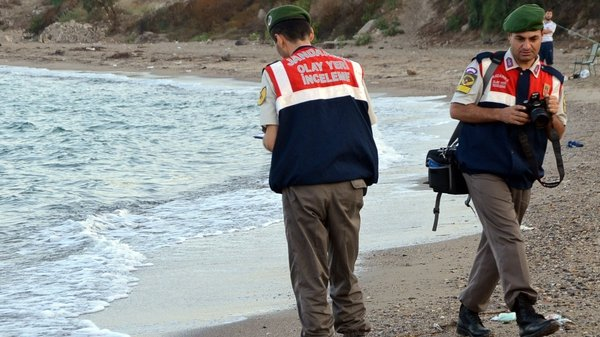 Turkish police at the scene where the body of a three-year-old refugee washed up on a beach