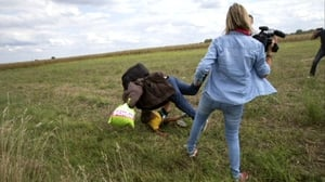 The woman can be seen tripping a man who was running with a child in his arms