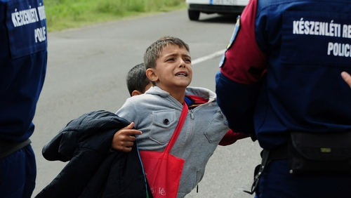 Police officers hold a child after a crowd broke out of at a refugee collection point near Roszke at the Hungarian-Serbian border
