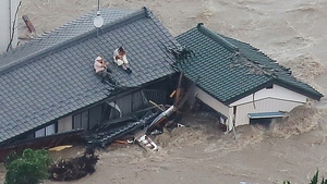 Local residents wait to be rescued on the roof of their home in a flooded area in Joso