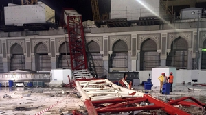 Saudi emergency teams stand next to a construction crane after it crashed into the Grand Mosque  oin Mecca