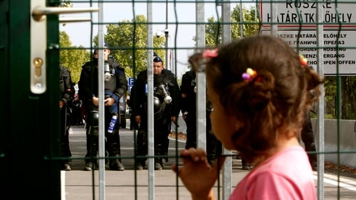 Hungarian police block a street towards the closed border crossing between Serbia and Hungary in Roszke