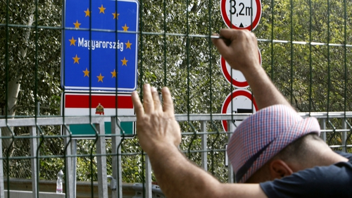 A man holds onto a fence at closed border crossing between Serbia and Hungary in Hogros on the Serbian side