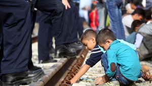 Children play near policemen standing guard at a railway station near the official border between Serbia and Croatia