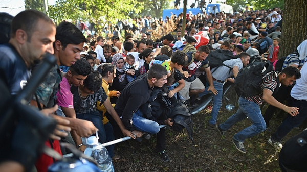 Migrants force their way through police lines at Tovarnik station to board a train bound for Croatia