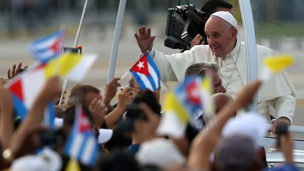 People wave Cuban and Papal flags at Pope Francis ahead of his mass at Revolution Square in Havana