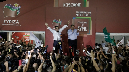 Syriza leader Alexis Tsipars (L) and leader of Independent Greeks 'ANEL' Panos Kammenos (R), wave to supporters