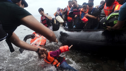 A young girl falls in the water as a boat carrying refugees lands on the beach at Sykamia on the Greek island of Lesbo