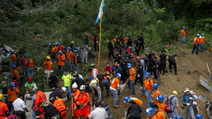 Rescue workers search for survivors of the landslide