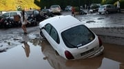 People walk past damaged cars after violent storms and floods in France