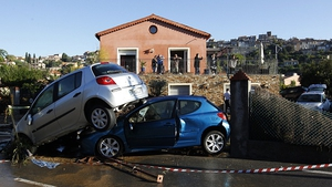 People look at the rubble and damaged cars in front of their house in Biot, France