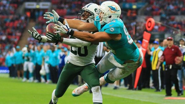 Marcus Williams (left) of the New York Jets intercepts a pass intended for Jordan Cameron of the Miami Dolphins