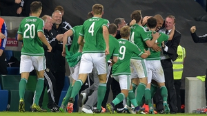 Josh Magennis and team mates mob Michael O'Neill after their second goal
