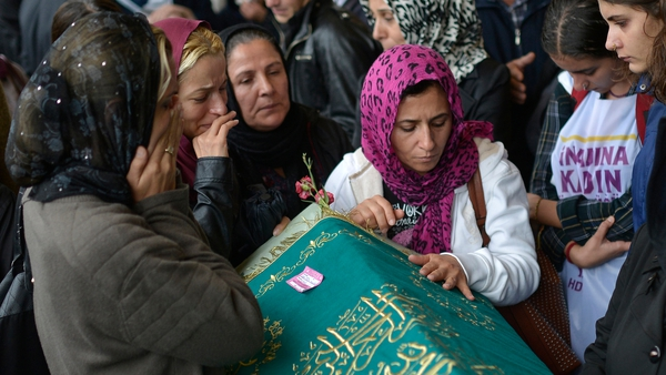 People mourn near by the coffin of one of the victims of the blast