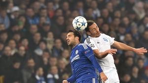 Chelsea's Cesc Fabregas challenges Dynamo Kiev's Ukrainian midfielder Serhiy Rybalka in the air at NSK Olimpiyskyi