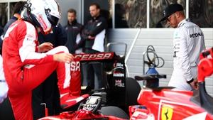 Lewis Hamilton checks out Sebastian Vettel's Ferrari's car as he climbs out in Sochi, Russia
