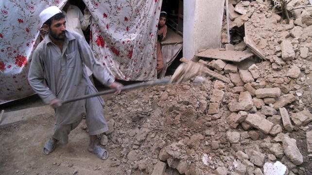 A Pakistani man removes debris after the 7.5 magnitude earthquake