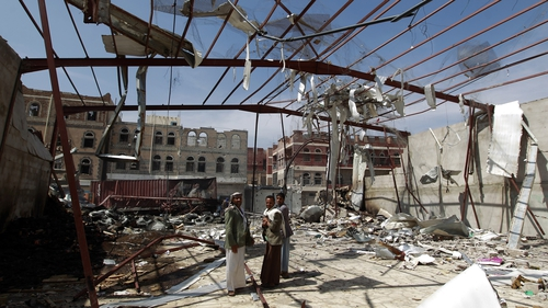 Yemeni men stand amid the rubble of a food storage warehouse following air strikes in the capital Sanaa