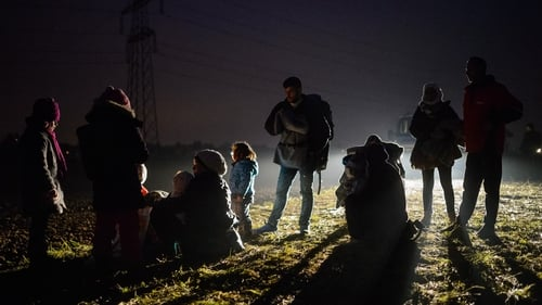 Migrants and refugees rest as they wait to board buses to go to a refugee center after crossing Croatian-Slovenian border in Rigonce