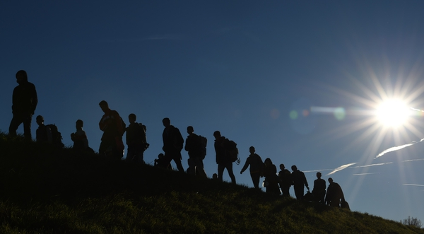 A group of people cross from Austria into Germany